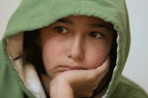young girl green hoody worried look